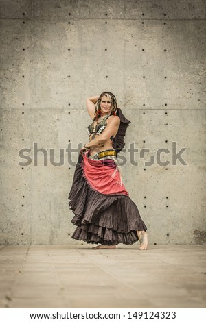 Tribal fusion belly dance costume with 25 yard skirt, fringe and kuchi belt with coin and shell bra, typically accessorized with metal earrings, choker type necklace, multiple arm bands and rings.