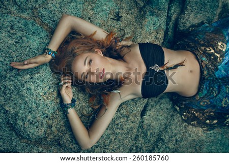 Tribal style girl on the stone rocks - stock photo