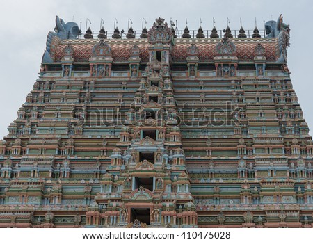 Trichy, India - October 15, 2013: Top half of the massive Rajagopuram of Ranganathar Temple. Eight levels and the long top, the Vimanam. A wall of pastel colors, pillars and statues. - stock photo