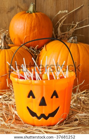 Trick or treat Halloween candies in the barn with orange pumpkins - stock photo
