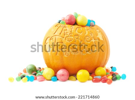 Trick or treat Halloween pumpkin filled with multiple colorful candies and sweets, composition isolated over the white background - stock photo