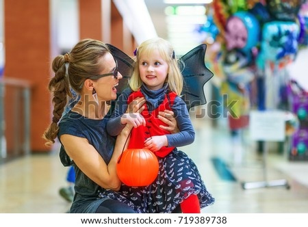 Trick or Treat. Portrait of smiling elegant mother and daughter in bat costumes on Halloween at the mall