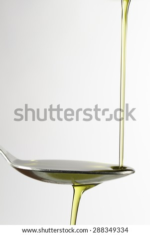 Trickle of extra-virgin olive oil on a spoon