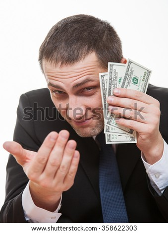 Tricky businessman becking somebody and holding dollars, white background