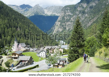 TRIENT, SWITZERLAND - AUGUST 31: Backpackers looking at Trient town, with Fontanabran mountain in the background. The village is on a stage of the popular Mont Blanc tour. August 31, 2014 in Trient. - stock photo