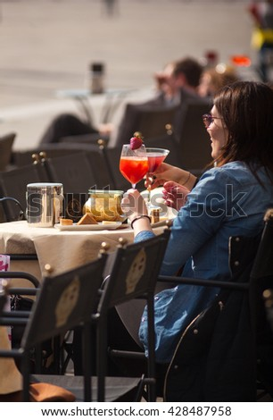 TRIESTE, ITALY - APRIL, 28: Girlfriens drinking a cocktail sitting in the outdoor coffee bar on April 28, 2016
