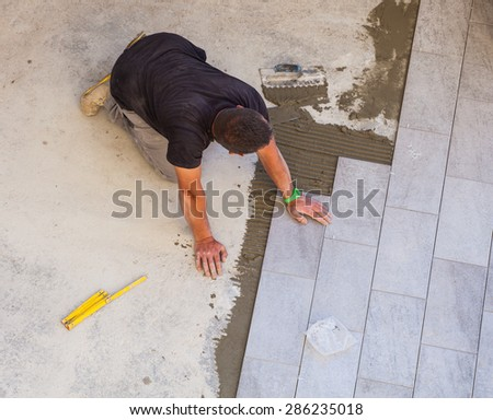 TRIESTE, ITALY - APRIL, 22: Worker Installing ceramic floor tiles on April 22, 2015