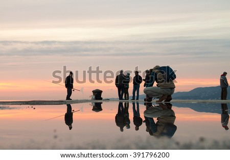 TRIESTE, ITALY - FEBRUARY, 25, 2016: Photo with reflection as a photographer takes pictures 4 fishermen at sunset with clouds, 1 man turned away and did not want to watch the scene.
