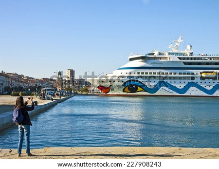 TRIESTE, ITALY - OCTOBER 26, 2014. Girl takes a mobile shot of a cruise ship moored at the quayside of Trieste harbor