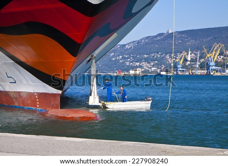 TRIESTE, ITALY - OCTOBER 26, 2014 Two workers clean and make maintenance service to the anchor of a passenger ship moored at Trieste quayside