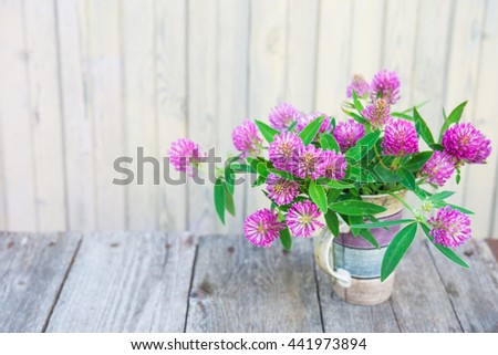 Trifolium pratense. Clover flowers on wooden table. Beautiful purple wildflower bouquet.  Medicinal plants.