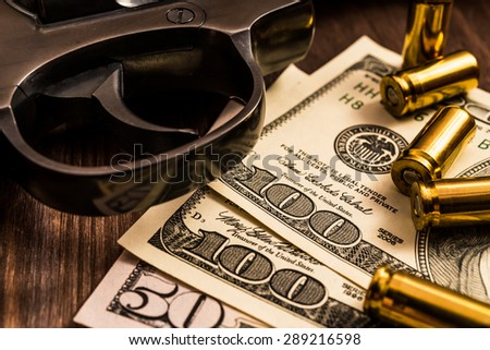 Trigger of a revolver with cartridges and money on the wooden table. Close up view - stock photo