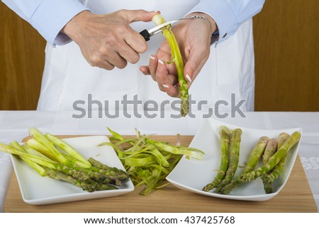 Trim and peel asparagus in the kitchen by a chef doing it with her hands and a manual peeler - stock photo