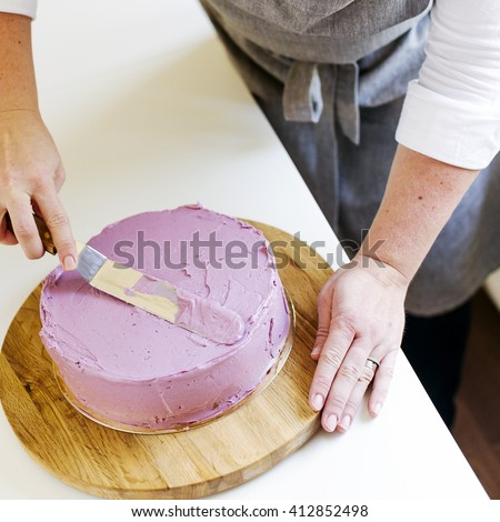 trim the cream icing on a lilac cake with a spatula - stock photo
