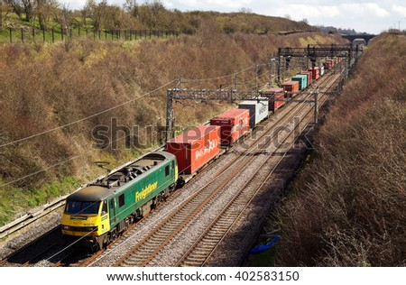 TRING, UK - APRIL 5: A Freightliner intermodal train passes Tring cutting heading towards the city of Manchester on April 5, 2016 in Tring. Freightliner operate a fleet of 80 locos & 1400 wagons