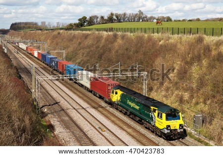 TRING, UK - APRIL 5: A Freightliner operated intermodal freight train passes through a deep cutting on route to London on April 5, 2016 in Tring. Freightliner operate a fleet of 80 locos & 1400 wagons