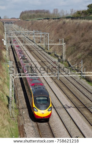 TRING, UK - APRIL 5: A Virgin operated class 390 EMU Pendolino express passenger train heads towards London along the busy WCML with a fast commuter service on April 5, 2016 in Tring