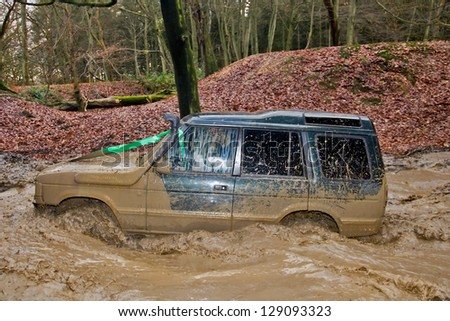 TRING, UK - NOVEMBER 25: Members of the Burnham Off Road club take a Land Rover Discovery through a water filled bombhole during the winter trialing competition event on November 25, 2012 in Tring