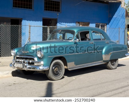 TRINIDAD, CUBA - DECEMBER 5:  An american vintage car is parked along a blue house,on december 5, 2014, in Trinidad, Cuba  - stock photo