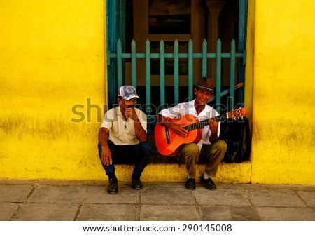 TRINIDAD, CUBA - DECEMBER 24, 2013: An unidentified street musician and another unidentified man sitting by the wall of an old yellow building in the historic part of Trinidad, Cuba on Christmas Eve. - stock photo