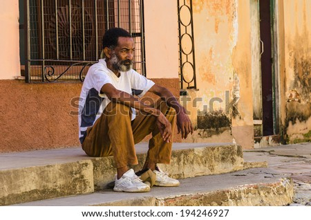 TRINIDAD, CUBA - DECEMBER 7, 2013: Cuban man resting in shadow on street of Trinidad, where temperature even in winters is often above 30 Celsius degrees.