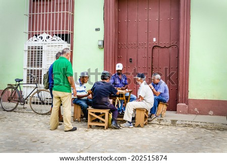 TRINIDAD, CUBA - DECEMBER 7, 2013: Old mans on the street of Trinidad playing domino, which is typical game for Cubans who often gather to play it outdoor what attracts many tourists  - stock photo