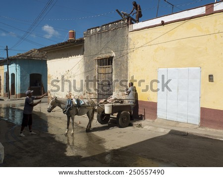 TRINIDAD, CUBA, DECEMBER 5: Three construction workers with a mule pulling a carriage  , on december 5, 2014 in Trinidad, Cuba. - stock photo