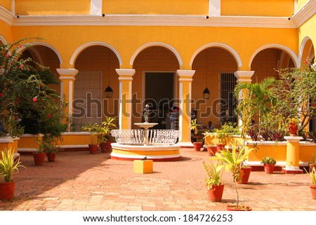 TRINIDAD, CUBA, FEBRUARY 25, 2014:  Colorful courtyard inside a museum with fountain and plants, a tourist destination in Trinidad, Cuba, on February 25, 2014