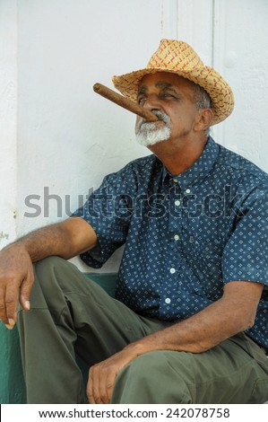TRINIDAD, CUBA - MAY 26, 2013 Cuban local man smoking cigar and posing to photos while sitting on street in UNESCO protected city of Trinidad, Cuba. - stock photo