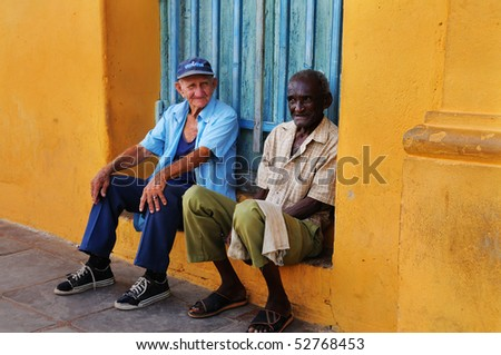 TRINIDAD, CUBA - OCT 25. Two senior men sitting in colorful facade. Trinidad was declared UNESCO World Heritage Site in 1988. Taken on oct 25, 2008 in Trinidad, Cuba.