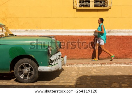 TRINIDAD - FEBRUARY 24: Streets of Trinidad with classic old car and woman walking on February 24, 2015 in Trinidad. Old American cars are iconic sight of Cuba street. - stock photo