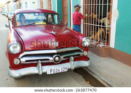 TRINIDAD - FEBRUARY 24: Streets of Trinidad with classic old car on February 24, 2015 in Trinidad. Old American cars are iconic sight of Cuba street. - stock photo