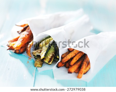 trio of carrot, zucchini, and sweet potato fries wrapped up in wax paper cones - stock photo
