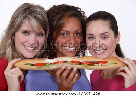 trio of girls eating giant sandwich - stock photo