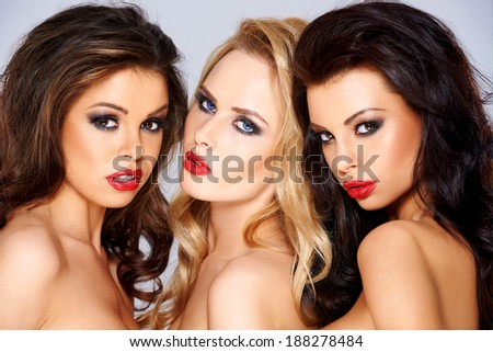 Trio of gorgeous sexy tantalising young women flirting with the camera with sensual seductive expressions