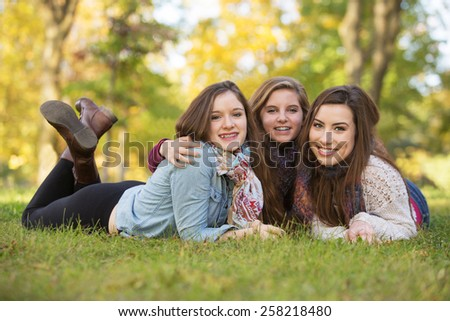Trio of happy teen girls laying down on grass - stock photo