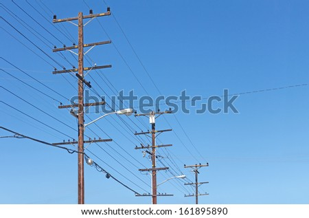 Trio of telephone utility poles, cables, streetlights, and clear blue sky background. Neat rows of parallel distribution wires connected to three tall wood posts. Perspective view. - stock photo