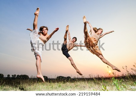 Trio of yang ballet dancers perform outdoor on sunset. - stock photo