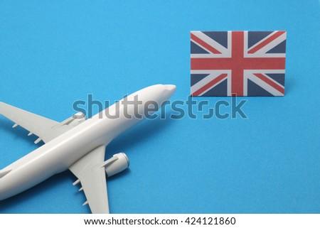 Trip by airplane to United Kingdom. Miniature airplane flies toward the flag of United Kingdom. - stock photo
