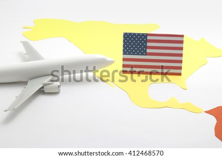 Trip by airplane to United States of America. Miniature airplane flies toward the flag of United States of America.  - stock photo