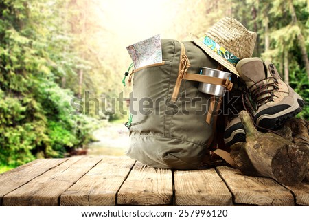 trip time and free space on wooden table with big backpack  - stock photo