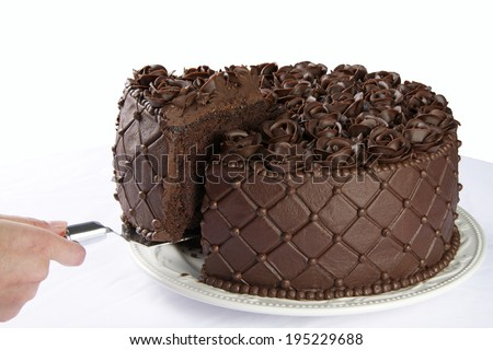 Triple Chocolate Cake with frosting roses being served sliced from the cake - stock photo