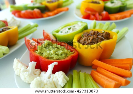 Triple dips with avocado guacamole, spicy tomato sauce and cashew chive sour cream, served with cauliflower, celery, carrots, cucumbers and red peppers - raw vegan healthy party food - stock photo