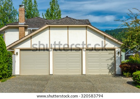 Triple doors garage with nicely paved long driveway. North America.