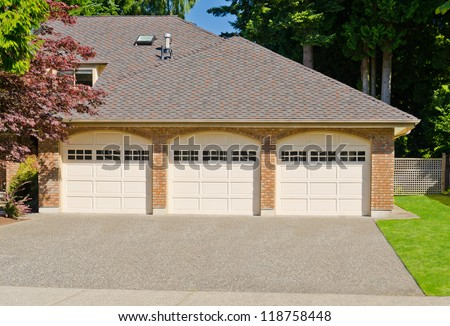 Triple doors garage with wide long driveway. - stock photo