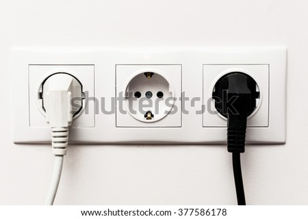 Triple electrical socket on white wall with two plugged cables - stock photo