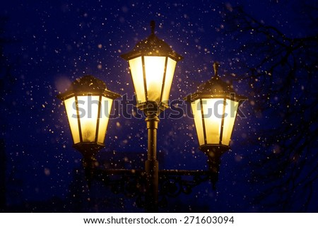 Triple lantern on a dark blue night sky and falling snow                           - stock photo