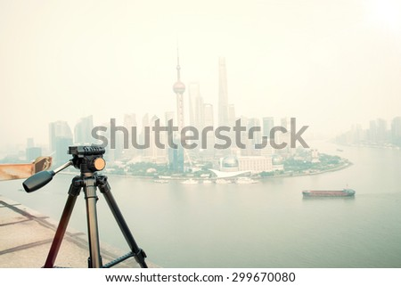 Tripod on the background of the modern city - stock photo