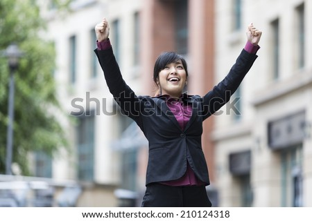 Triumphant Chinese businesswoman with arms raised. Concept about an Asian business woman celebrating success. - stock photo
