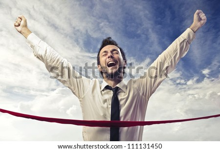 Triumphing businessman crossing the line - stock photo